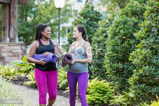 Two multi-ethnic pregnant women in their 30s, walking through a garden in the city, carrying yoga mats, conversing on their way to a yoga class for some exercise and relaxation.