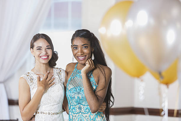 two multi-ethnic teenage girls dressed for special event - prom stock photos and pictures