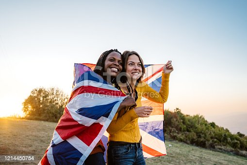 Two young pretty multi-ethnic women holding British flag on meadow.
