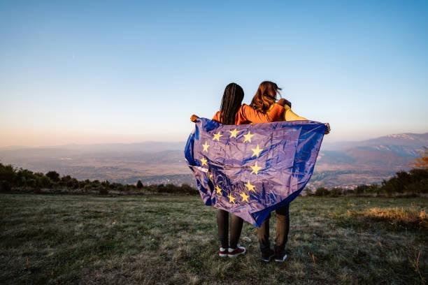 Two multi-ethnic women holding European Union flag stock photo