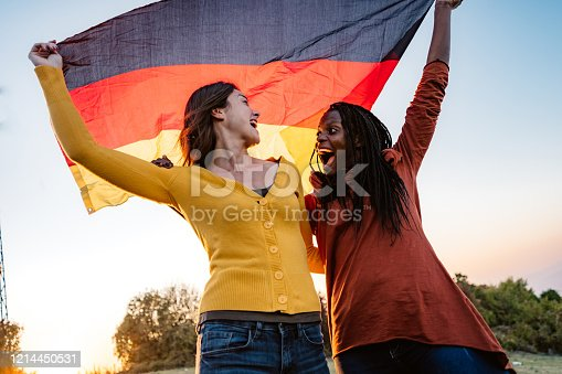 Two young pretty multi-ethnic women holding German flag on meadow.