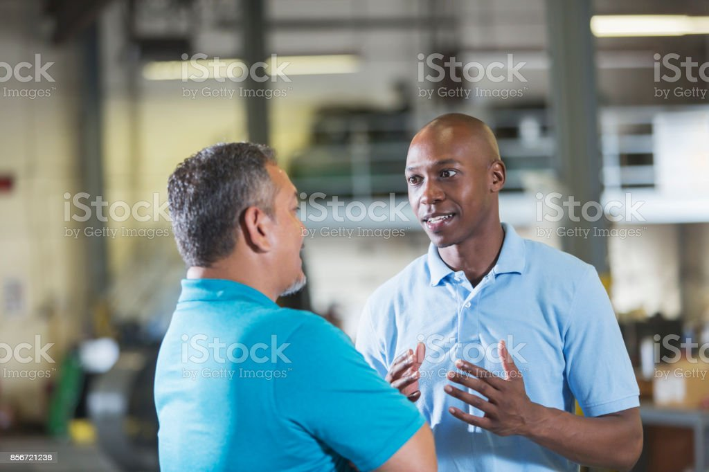 Two multi-ethnic workers in a workshop talking stock photo