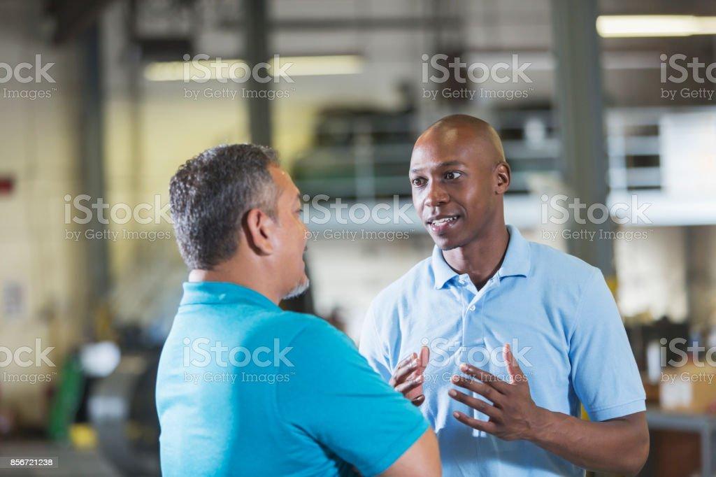 Zwei multi-ethnischen Arbeiter in einer Werkstatt im Gespräch – Foto
