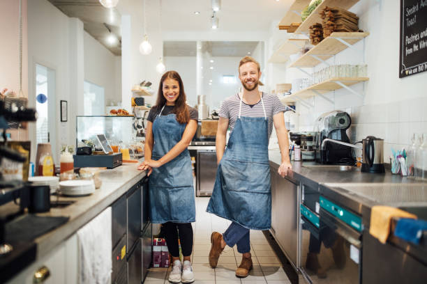 Two  multiracial baristas in cafe kitchen stock photo