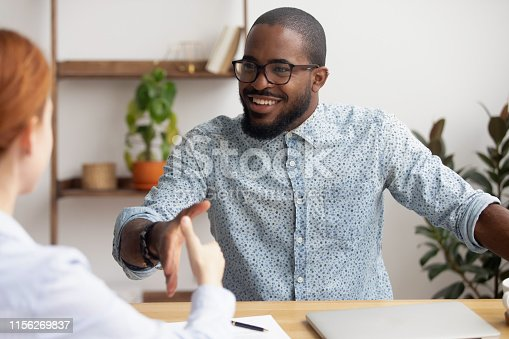 istock Two multiracial business partners handshaking focus on african-american employee 1156269837