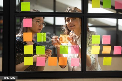 1144569896 istock photo Two multiracial female partners planning business project. 1193712991