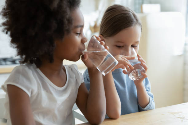 Two multiracial girls sit in kitchen feels thirsty drink water Two multi racial little girls sit at table in kitchen feels thirsty drink clean still natural or mineral water close up image. Healthy life habit of kids, health benefit dehydration prevention concept drinking water stock pictures, royalty-free photos & images