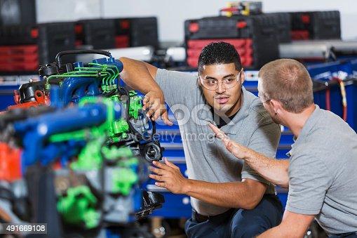 istock Two multi-racial men in auto mechanic school with engine 491669108