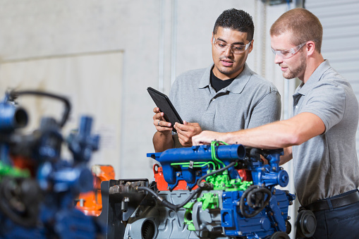 Two multi-ethnic young men in vocational school, taking a class on reparing diesel engines.  They are working on an engine that has had parts painted different colors for training purposes.  They are wearing safety glasses. The Hispanic man is reading a digital tablet.