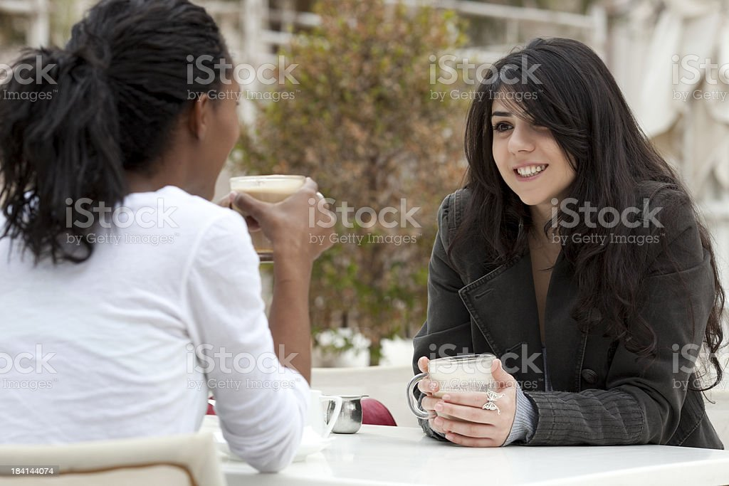 Two multiracial young girls in open-air cafe. royalty-free stock photo