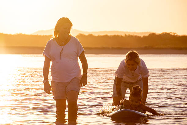 Two mum's help daughter surfing stock photo