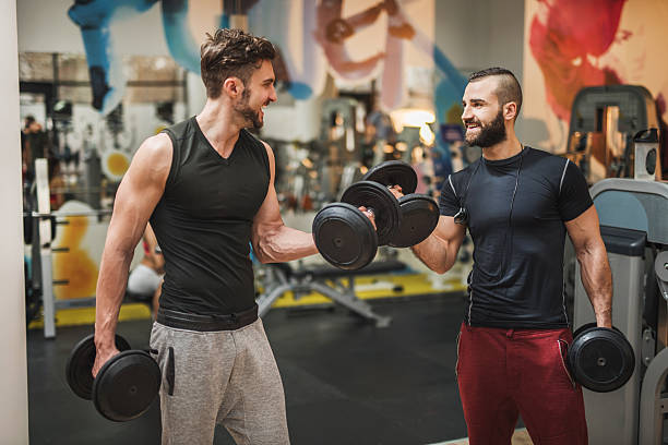 Two muscular build men having weight training in a gym. stock photo