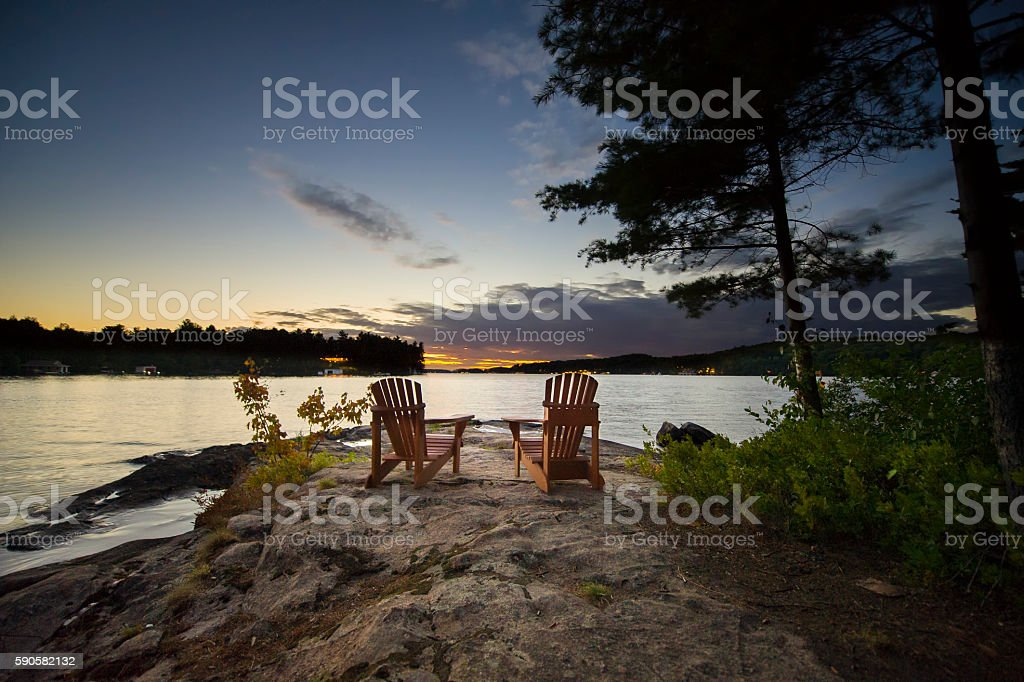 Two Muskoka chairs sitting on a rock at sunset stock photo