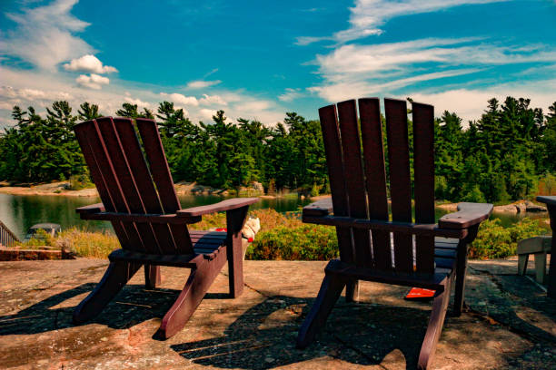 Two Muskoka chairs sitting on a wood dock facing a calm lake. Across the water is a white cottage nestled among green trees. stock photo