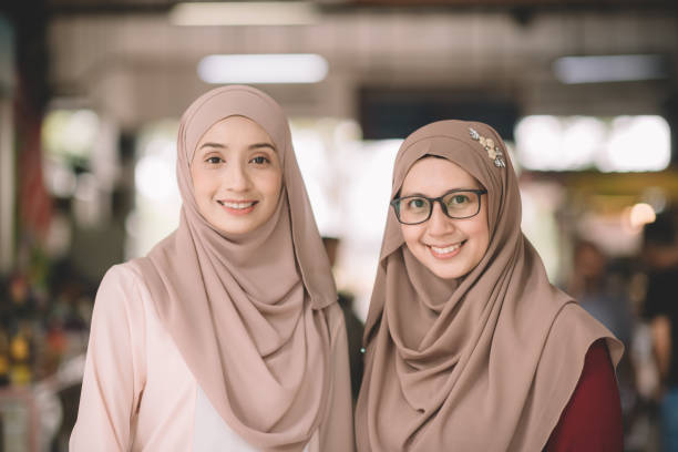 two muslim female malay ladies friend met up at wet market in the morning and greeting to each other stock photo