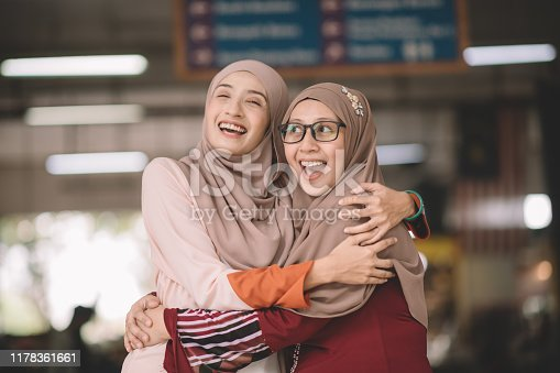 two muslim female malay ladies friend met up at wet market in the morning and greeting to each other