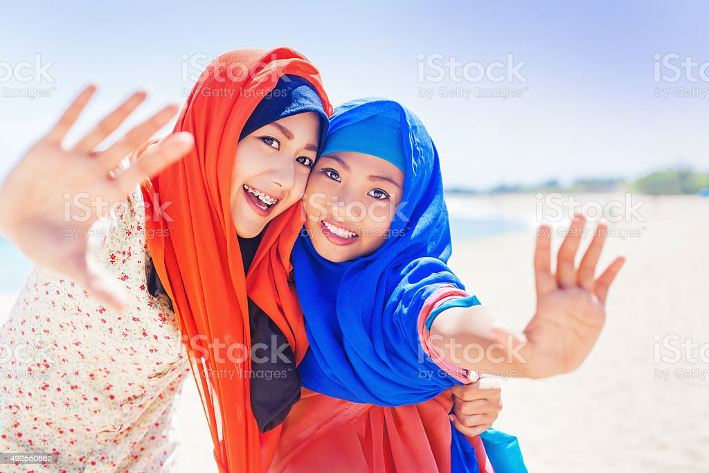 two muslim girls smiling at camera stock photo