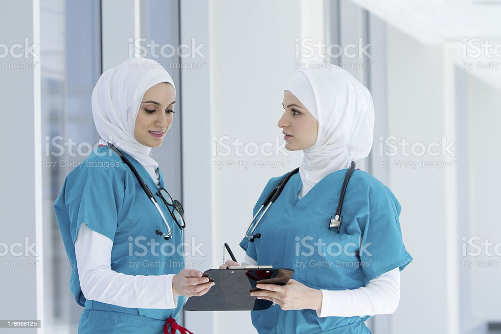 Two Muslim Health Care Professionals Talking stock photo