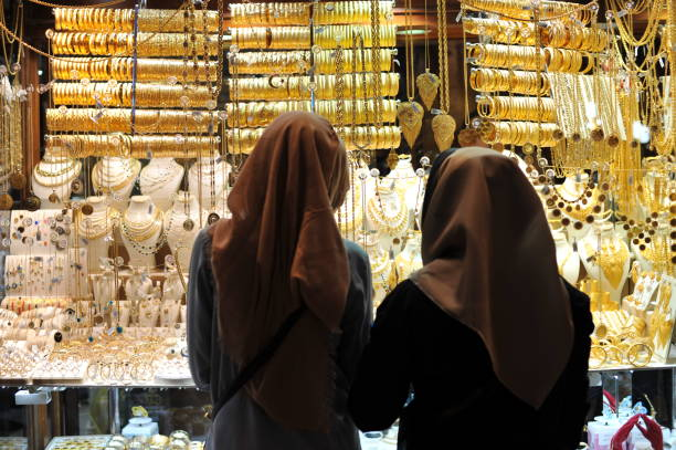 Two muslim woman with head scarves window shopping gold jewelry stock photo