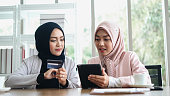 Two Muslim women in a cafe, shop online using electronic tablet