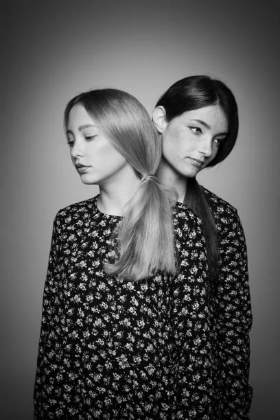 zwei geheimnisvolle mädchen mit ponytails in the same dress - siamesische zwillinge stock-fotos und bilder