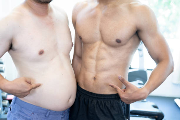 two naked men comparing belly fat and slim six pack - szczupły zdjęcia i obrazy z banku zdjęć