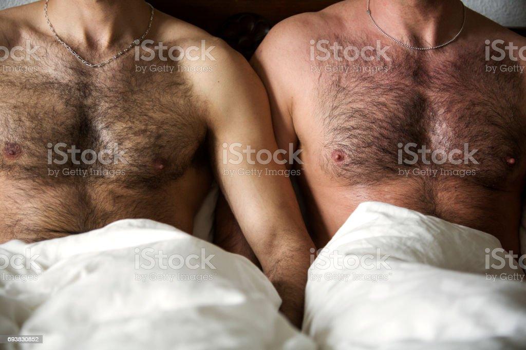 zwei nackte Männer mit behaarter Brust im Bett – Foto