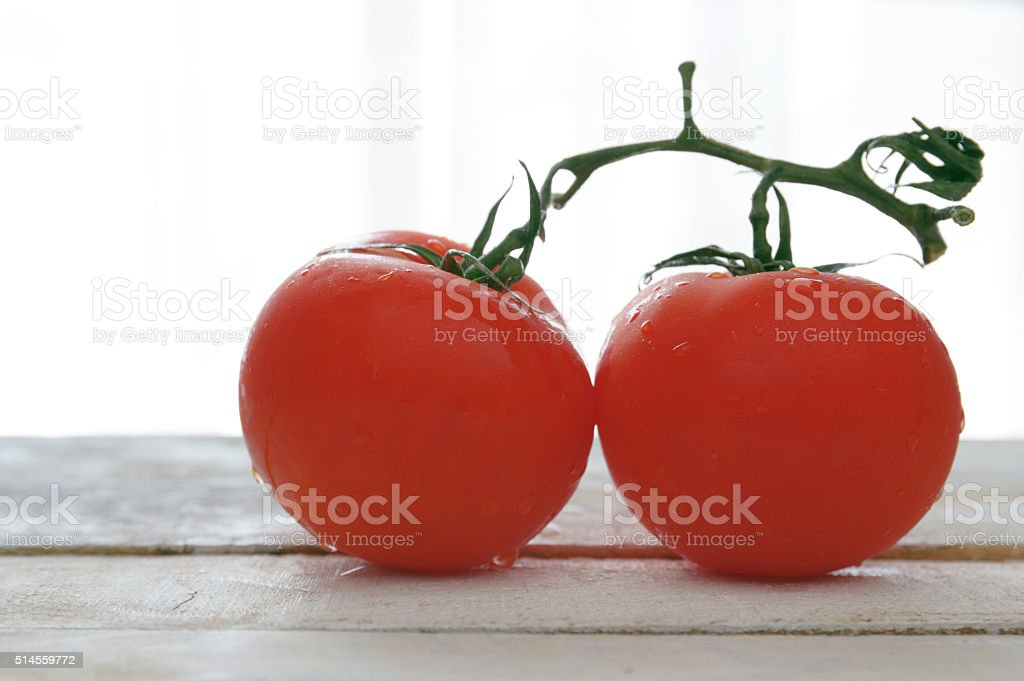 Two natural tomatoes on a white wooden table. stock photo