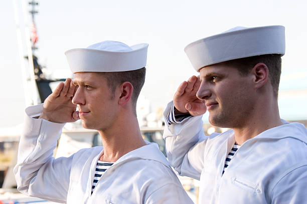 two navy sailors saluting on a ship - navy stock photos and pictures