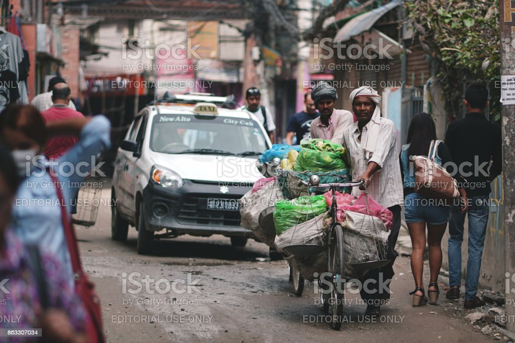Two Nepali Vegetables sellers Push Bicycle That Carry Many Fruits Across Crowded Thamel Street stock photo