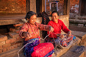 Nepali women spinning a wool in front of the house. Bhaktapur in Kathmandu valley. Nepal.http://bem.2be.pl/IS/nepal_380.jpg