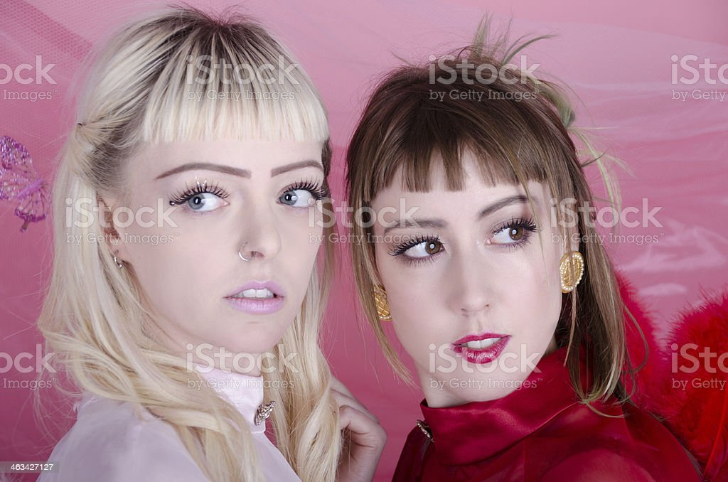 Two nervous young women as worried cherubs. royalty-free stock photo
