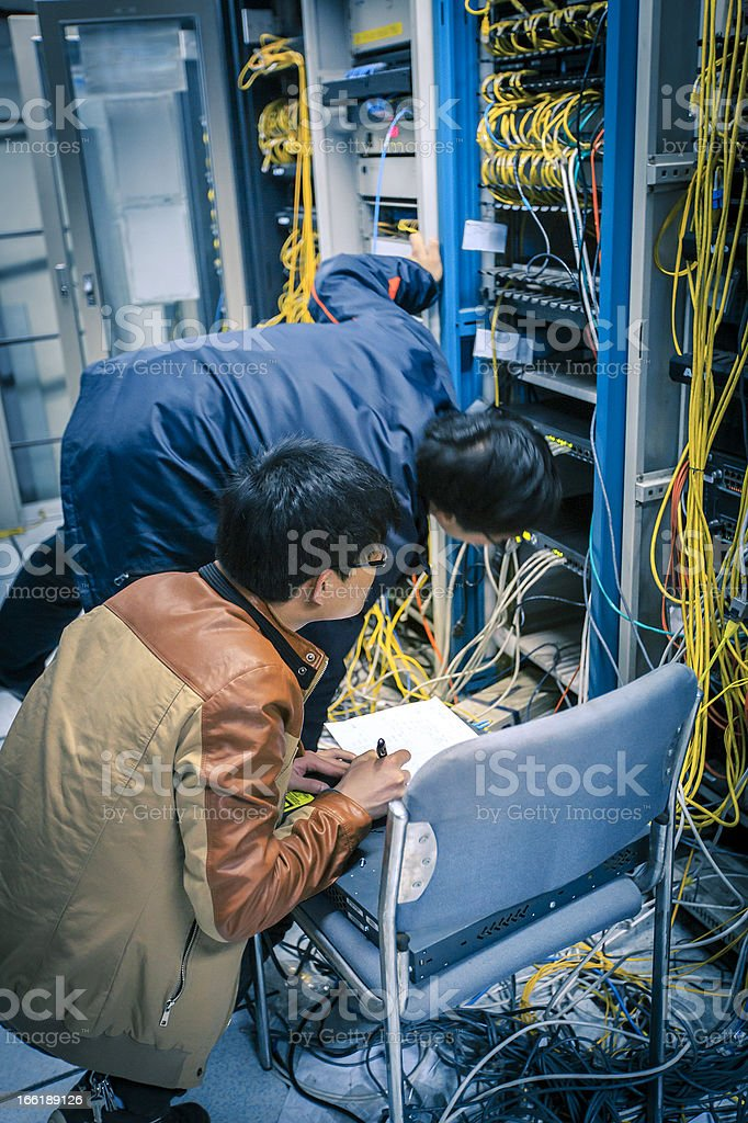 Two network administrators are working in the server room royalty-free stock photo