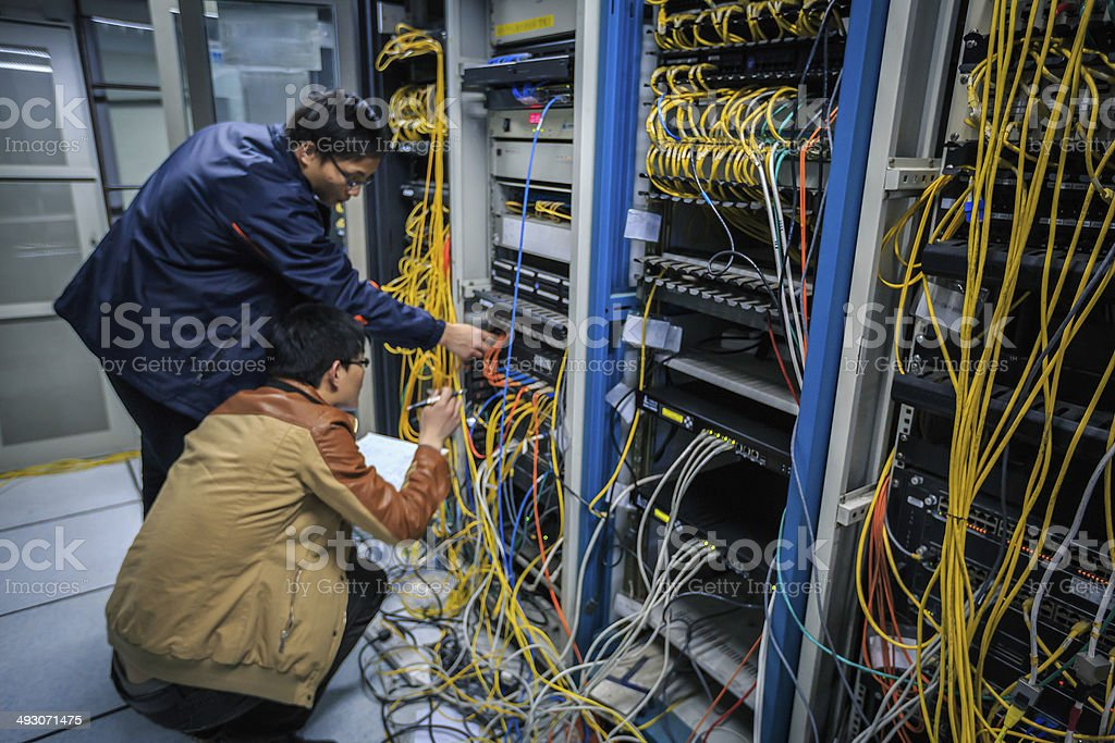 Two network administrators are working in the server room stock photo