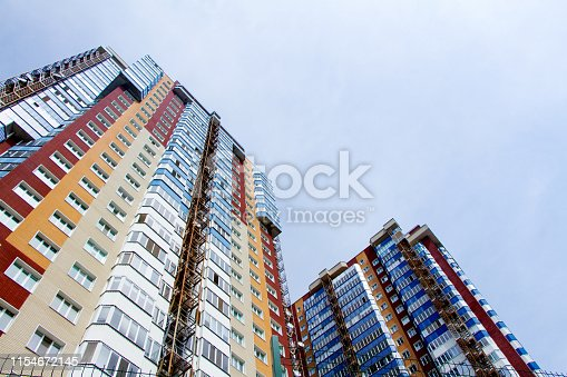 Two new blocks of modern apartments with balconies and blue sky in the background, free space for text
