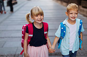 Smiling blond brother and sister holding hands while walking through town on their way to school