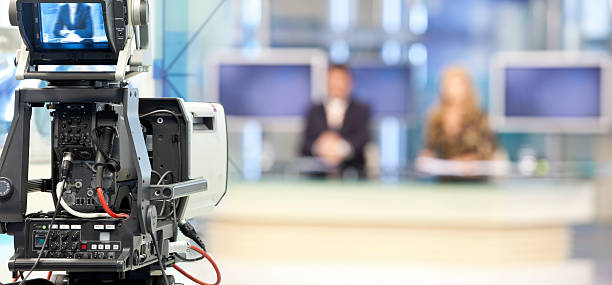 Two newsreader in front of television camera stock photo