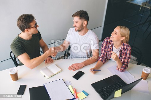 Two nice and cheerful guys sit in front one another and shake hands. They smile. Young blonde woman look at them and laugh. They are together in one room