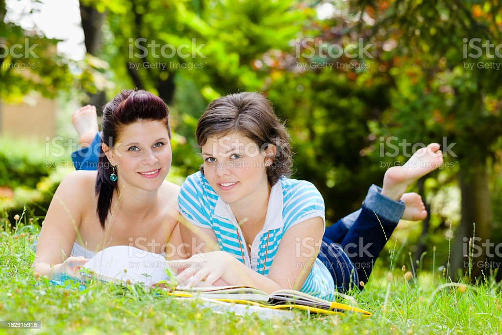 Two nice girls reading in a garden royalty-free stock photo