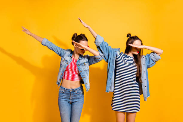 Two nice-looking good-dressed cute sweet gorgeous brunette hair lady stand isolated on yellow wall make dabbing movement stock photo