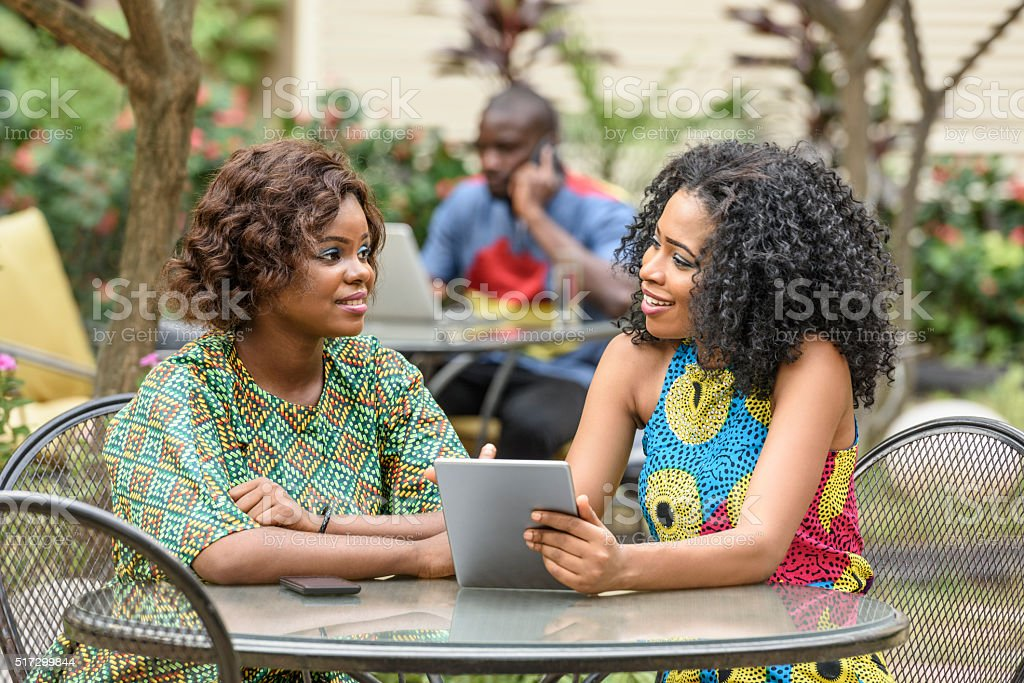 Two Nigerian women talking together with tablet stock photo