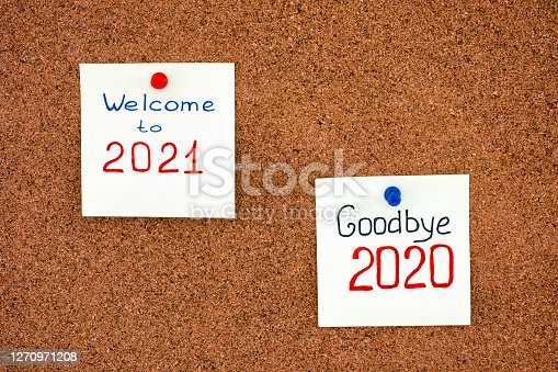 Two notes with phrases Goodbye 2020 and Welcome to 2021 on corkboard.