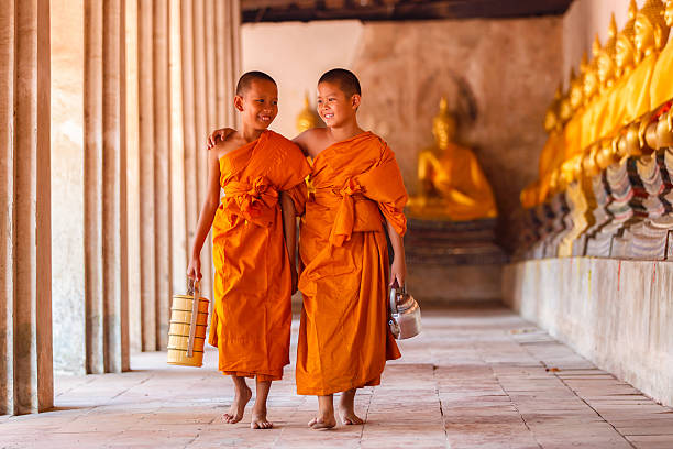Two novices walking and talking in old temple 스톡 사진