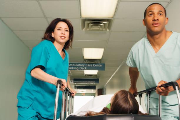 zwei krankenschwestern machenschaften gurney mit patienten im flur des krankenhauses - kinder die schnell arbeiten stock-fotos und bilder