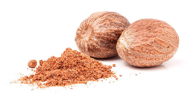 Two nutmeg whole  isolated on white background Two nutmeg whole and powder isolated on white background. nutmeg stock pictures, royalty-free photos & images
