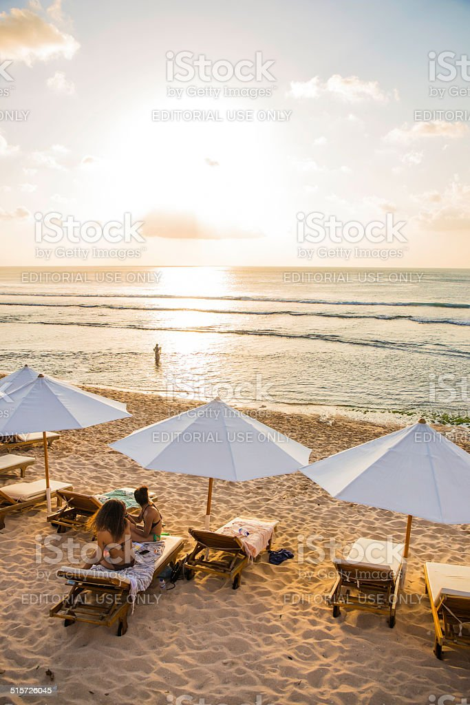 Two occidental woman and a local fisherman at sunset stock photo