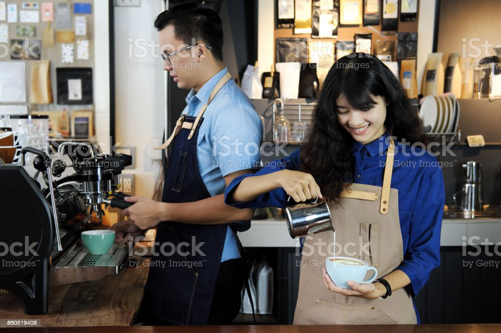 Two of asian barista making latte or cappuccino coffee in coffee shop. Cafe restaurant service, Small business owner, food and drink industry concept. stock photo