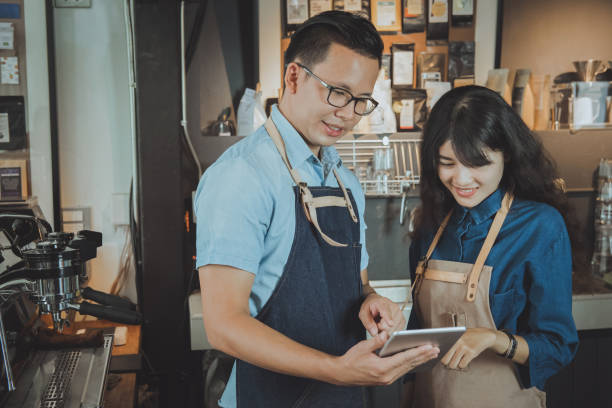 Two of asian baristas taking an order by digital tablet. Cafe restaurant service, food and drink industry concept. stock photo