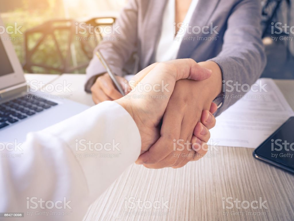 Two of businessman and businesswoman shaking hands in the meeting for success and agreement to express teamwork/togetherness and cooperation concept royalty-free stock photo