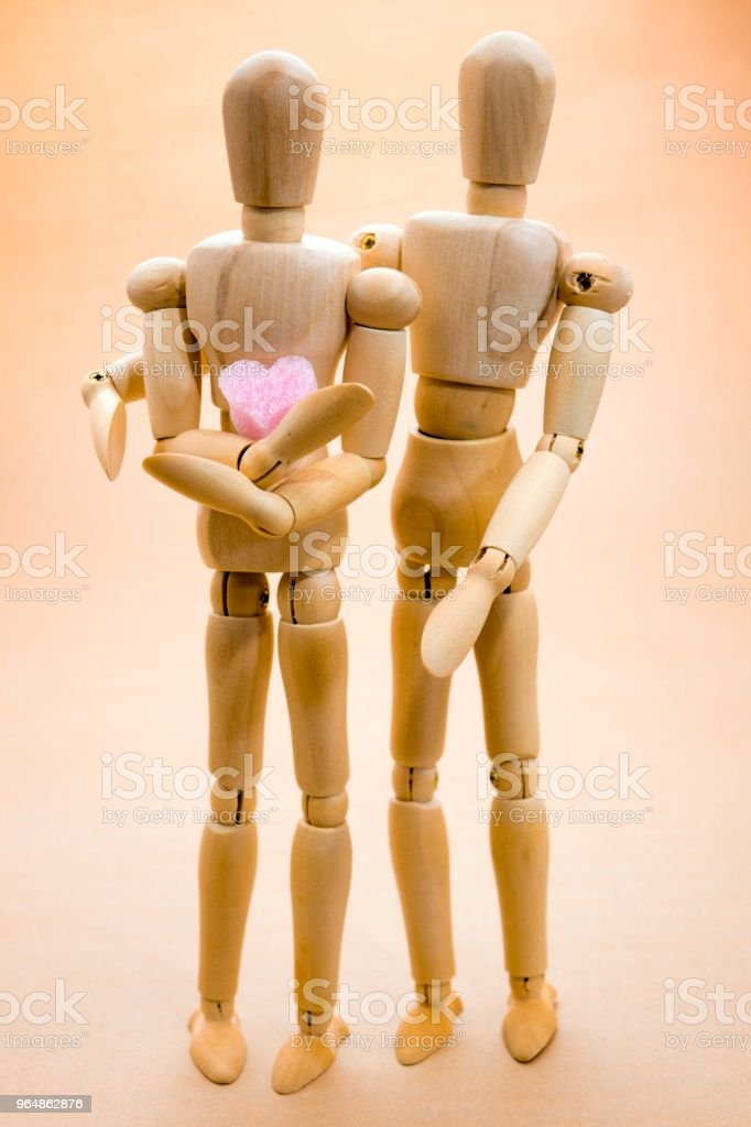 Two of wooden figure holding  a heart royalty-free stock photo